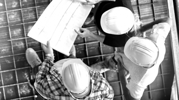 Building contractors on site in hard hats - DUAL Oliva